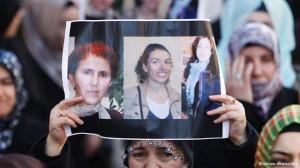 Woman holds up photos of Kurdistan's 'three flowers'