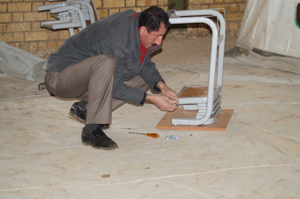 Teacher Mohammed fixing a broken desk for the pupils with a screwdriver before starting his class