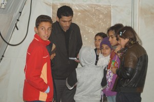 Children huddle against the cold in their refugee school tent and speak with  Hashlo