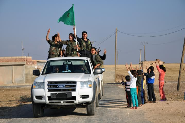 """Local kids in Tirbespiye also welcome home the YPG fighters with the famous YPJ slogan: """"Women, Life and Freedom"""""""