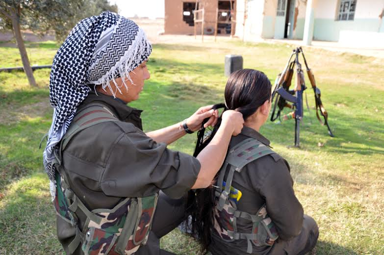 Two YPJ women at an outskirt village of Tirbespiye taking a rest during clashes with jihadist forces.