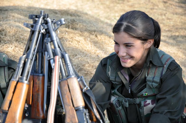 A YPJ fighter making a joke during a meeting before entering the battle ground on the outskirts of Tirbespiye.