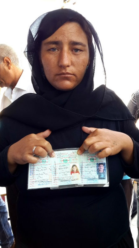 Sare holds ID cards of murdered family members. Her son Barzan, daughter Basima and husband Khalel were shot by ISIS terrorists. The rest of the family ran for their lives