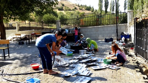 Ezidis washing up plates after lunch in Hilal school yard