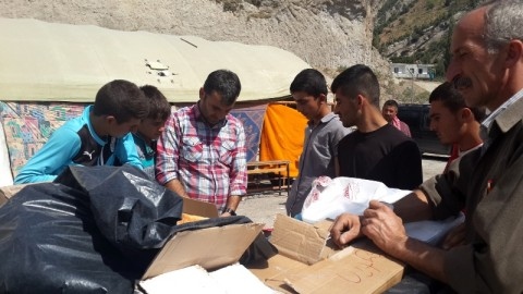 Roboski camp leader Ferhat Encu (plaid shirt) distributing food