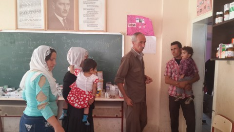 Roboski camp leader Lezgin Encu dispensing medicine for sick children