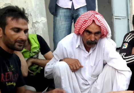 Namir Yousif Osman's (right) son was killed by the sword. Yezidi Ferhan Mahlo Khalil (left) is camp translator.