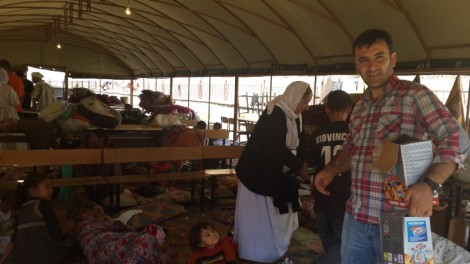 Ferhat Encu distributes food at Roboski school which welcomed 20,000 Yezidis