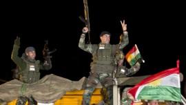 Peshmerga troops salute Kurds in north Kurdistan/Turkey, on way to join Kobani resistance; Pic Vadim Ghirda/AP