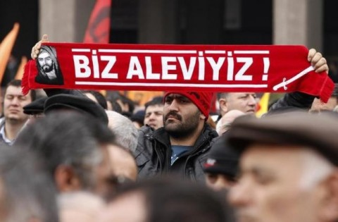 """A protester holds a banner reading """"we are alevi"""" as he and many others wait to hear the decision of the court in front of a courthouse in Ankara March 13, 2012. REUTERS/Umit Bektas"""