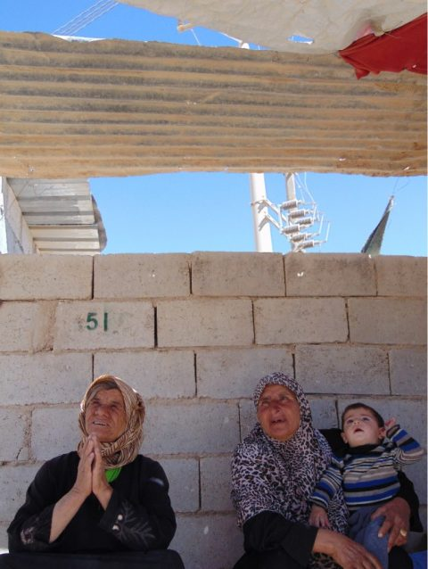 Women and child at the gate of Zaatari camp waiting for bus to nearby Mafraq town.