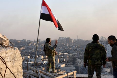 Syrian soldier gives victory sign in the devastated city of Aleppo